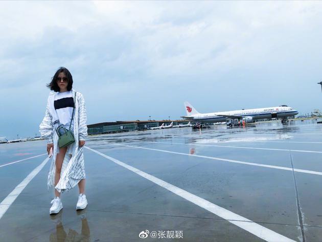 张靓颖乘早班机晒素颜照 戴墨镜穿长款外套配小白鞋