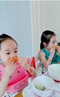 杨云晒双胞胎女儿吃橙子视频 欢欢乐乐戴围兜表情呆萌